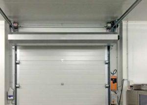 Ein Tor (mit wenig Platz) wird mit einem kompakten airStop-System von Masterveil abgeschirmt, in diesem Fall mit einem zusätzlich eingebauten Ventilator.